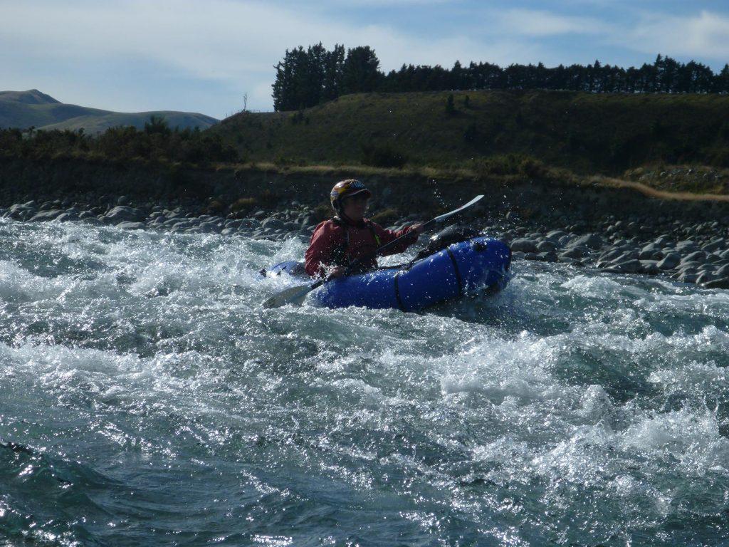 Carol, in her pack raft, runs a rapid.