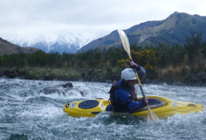 Murray breaks out of an eddy, snowy mountains in the background